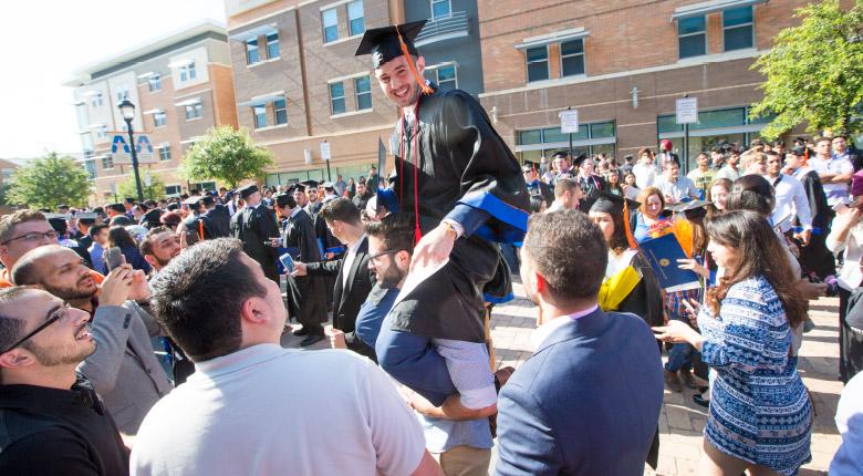 Students celebrating their graduation on the UTA campus.