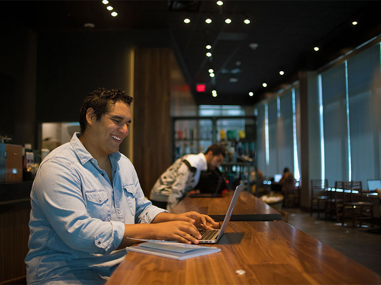 Student smiling and looking at laptop at a table inside campus Starbucks.