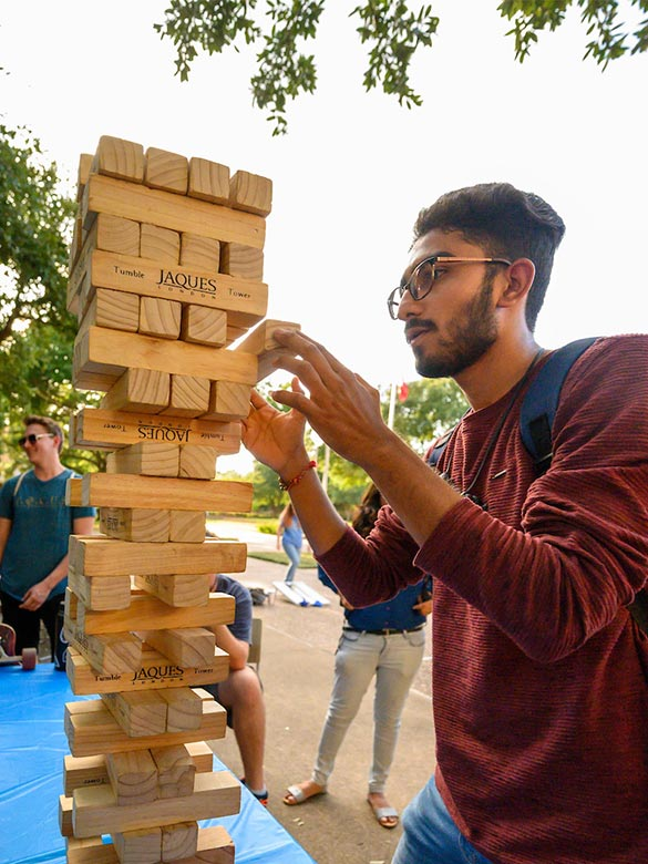 A student playing Big Jenga during UTA Libraries Fair.