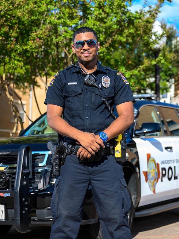 UTA Police Officer posing in front of UTA Police Vehicle.
