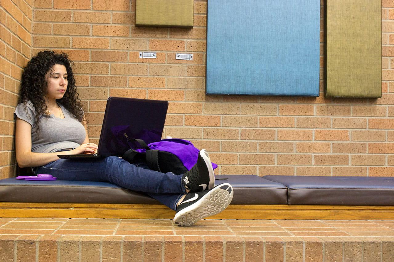 student studying laptop inside