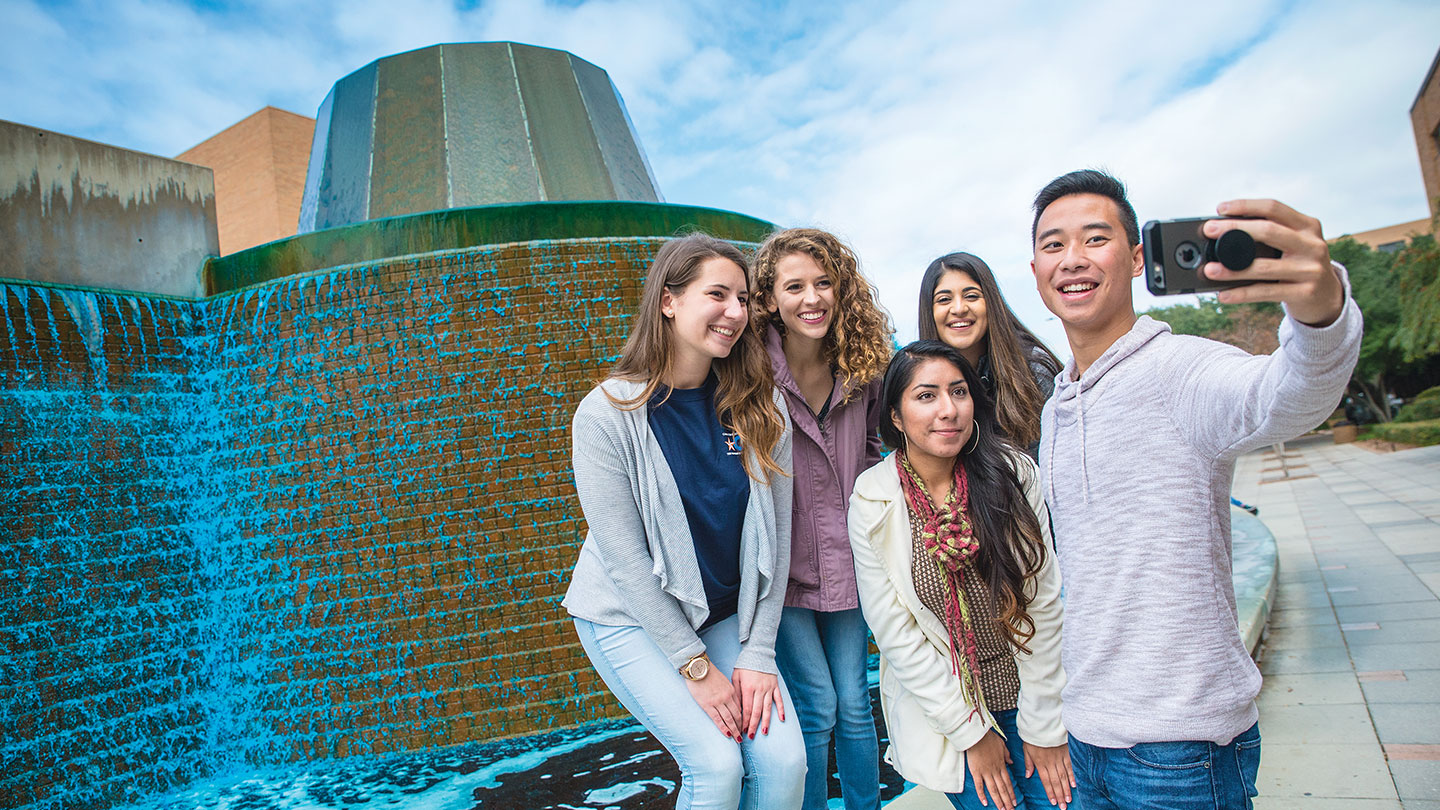 Students taking selfie in front of blue fountain during Homecoming