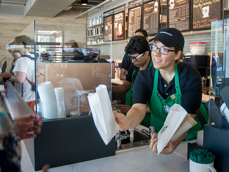 Starbucks employee handing out food to customers