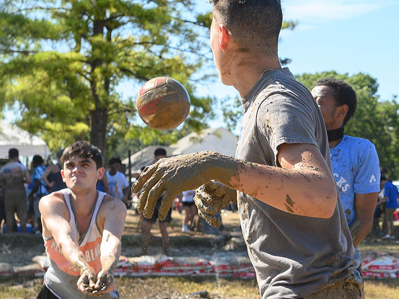 Students covered in mud playing volleyball at Oozeball