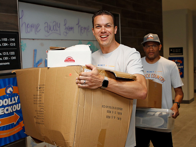 Volunteer carrying a box at Maverick Move-In day