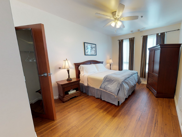 The Lofts at College Park  Bedroom furnished with a bed, cabinet, bedside table and closet
