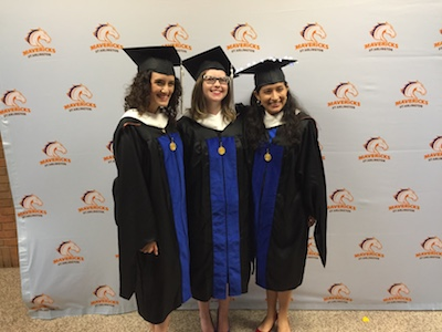 Three female students in regalia after their MA hooding