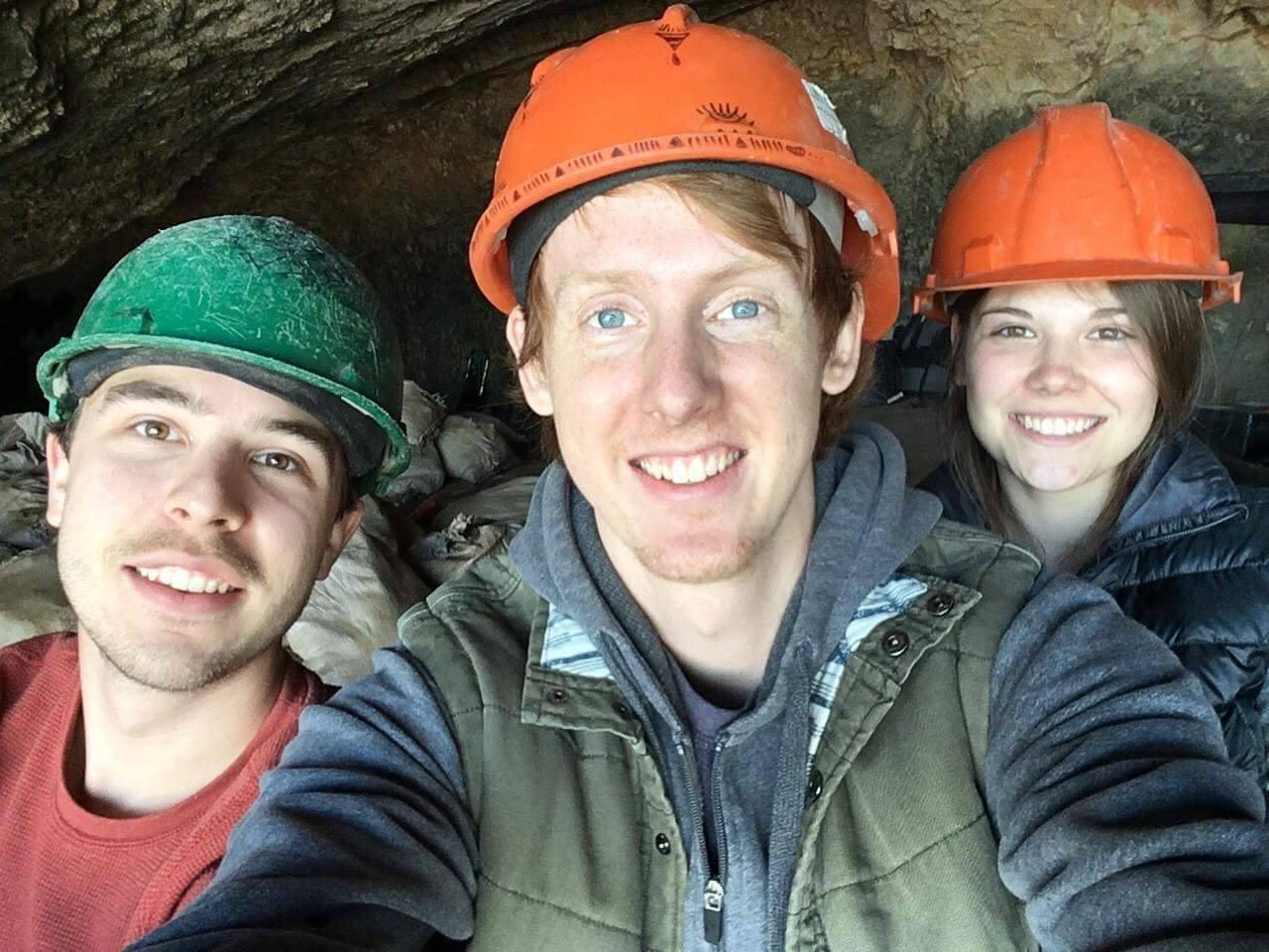 A photo of three people wearing orange hats .