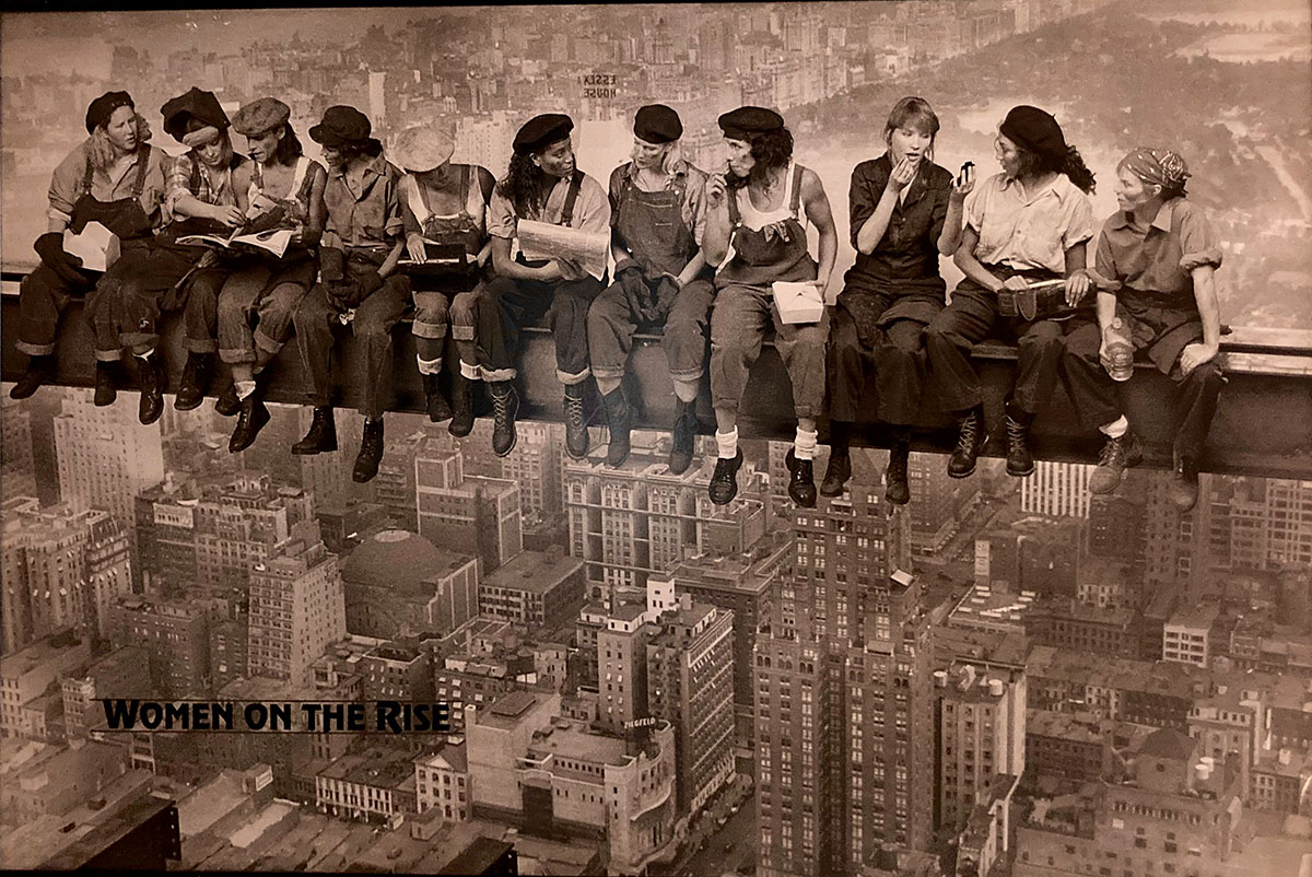 """Sepia color of several women dressed as 1940-1950s construction workers sitting on steel beam with a cityscape below and behind them.  The title Women On the Rise is in the bottom left corner."""" _languageinserted=""""true"""