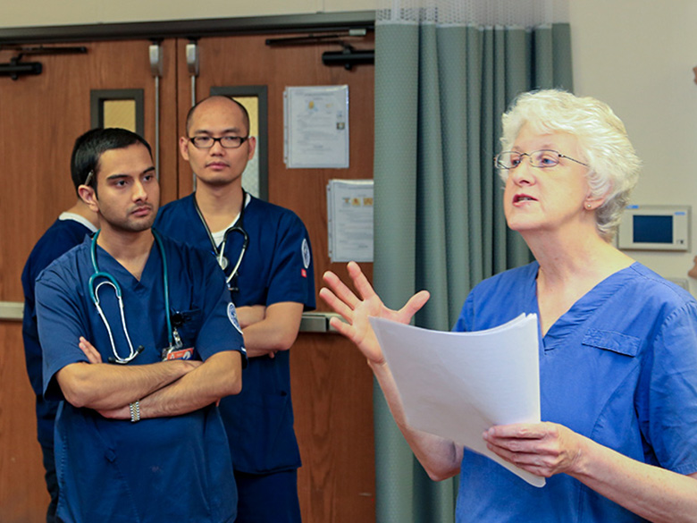 female instructor in scrubs speaking with male nursing students