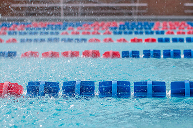 A swimming pool with red and blue plastic lane dividers.