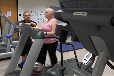 A student monitors a fit steps participant as she walks on a treadmill.