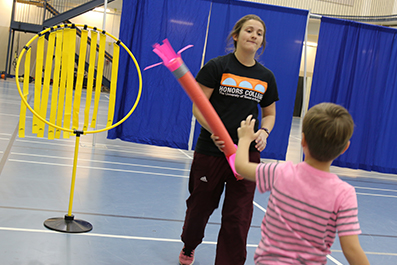 A Developmental Motor Cognition lab student works with a child in the Little Mavs Movement Academy.