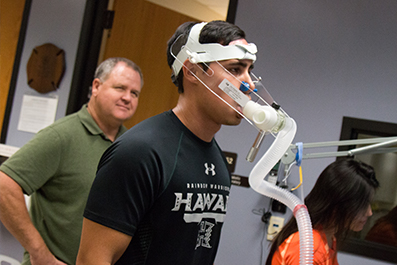 A runner wears a breathing tube and mask during a V O 2 max test.