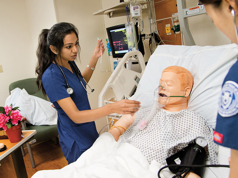 A student assists a simulated patient wearing an oxygen mask.