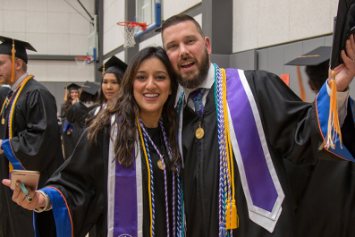 Two students wearing honors cords celebrate before a commencement ceremony.