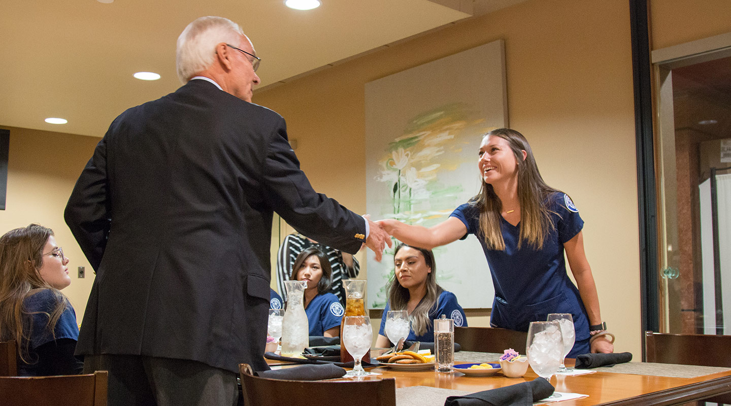 A donor shakes the hand of a nursing scholarship recipient at a formal dinner event.