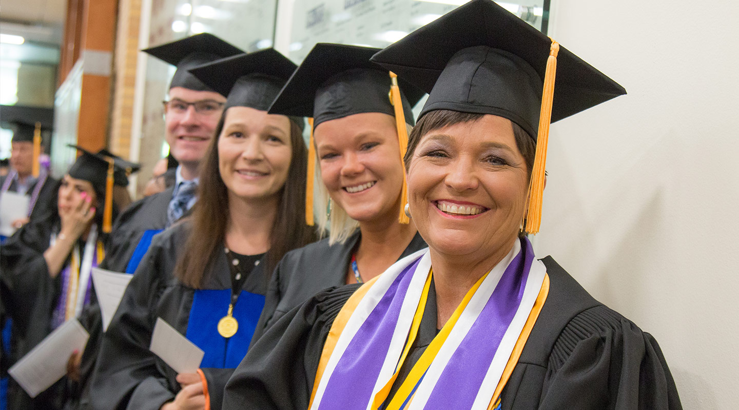 A group of four students wearing cap and gowns prepare for a graduation ceremony.