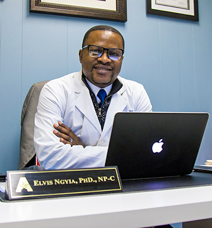 Male PhD Nurse Practitioner sitting in front of laptop