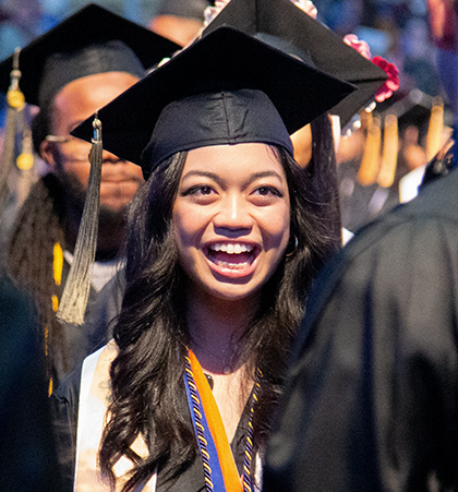 A student smiles as they walk down the aisle during a commencement ceremony.