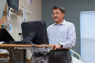 Dr. Yan Xiao working at computer in office