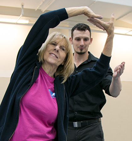 Ryan Hulla helps a paticipant stretch in the Center for Healthy Living and Longevity