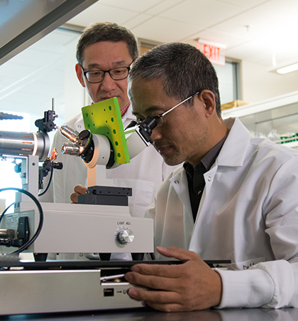 Two researchers in lab coats use a microscope to conduct an experiment