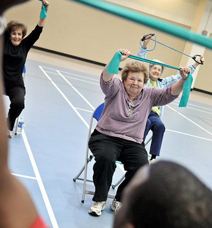 A group of older adults participate in a stretching exercise during an aerobics class.