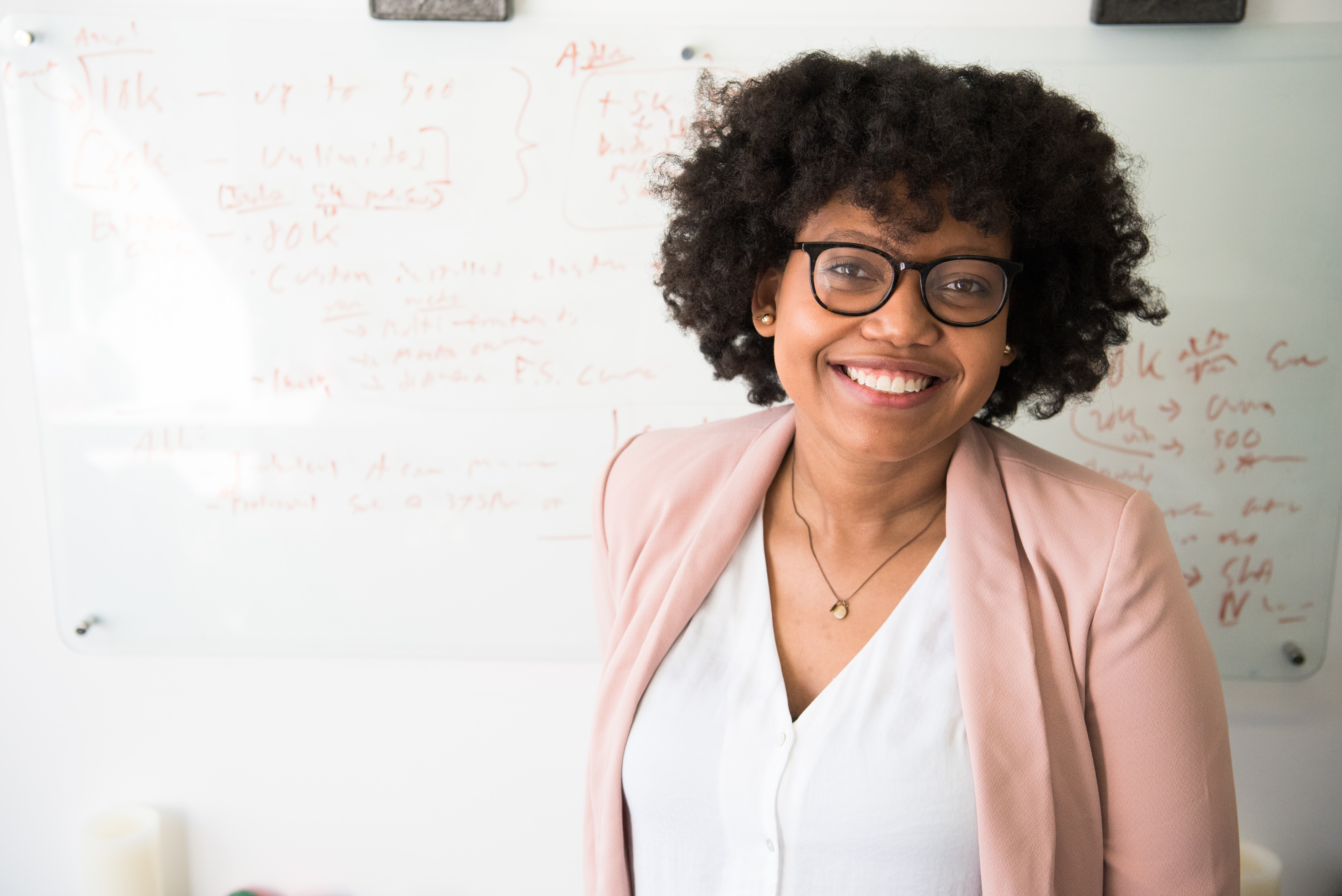 Teacher smiling for a photo while standing in front of a white board with classroom notes