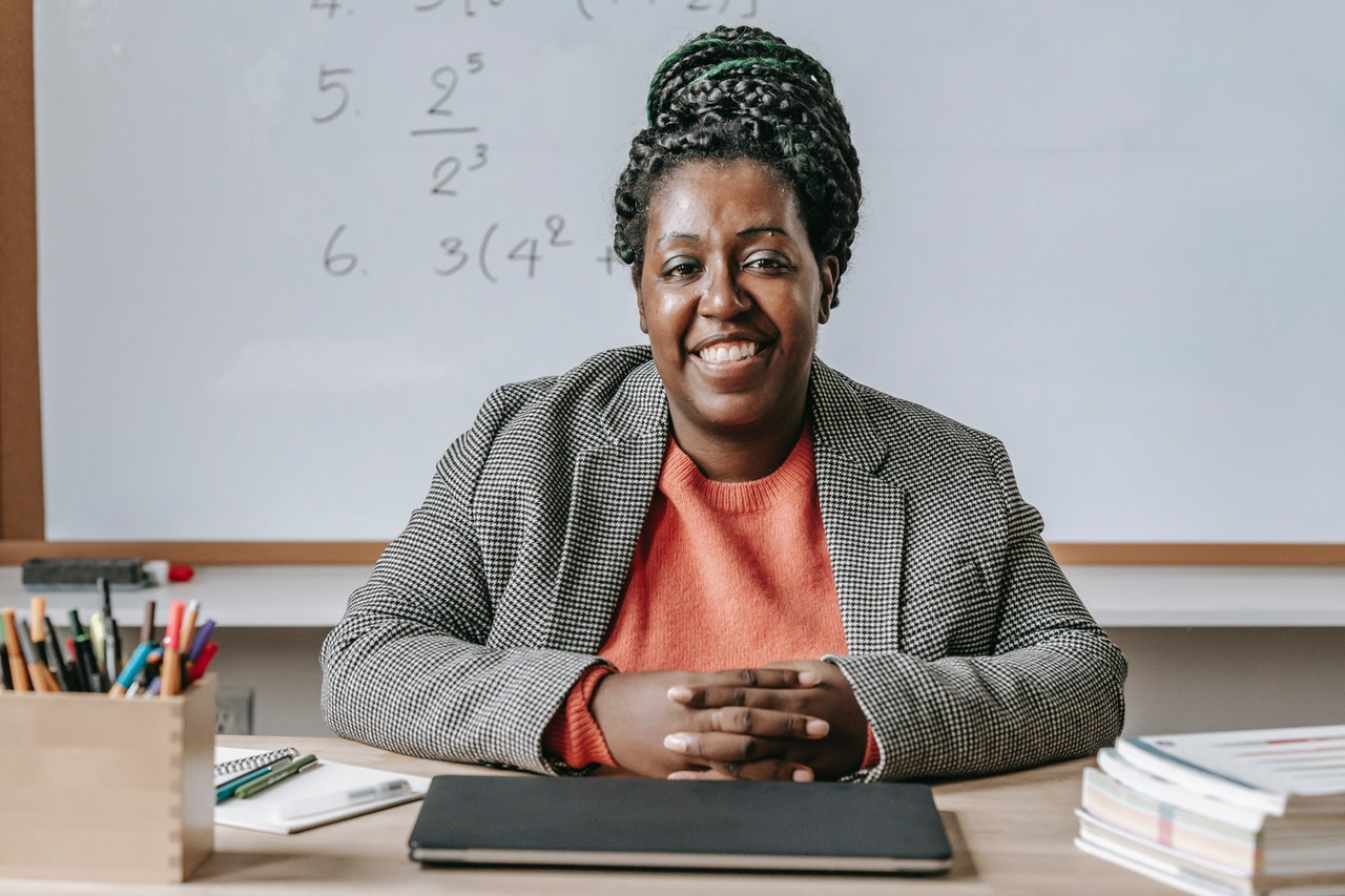 An educator sitting in a classroom and smiling for the camera.