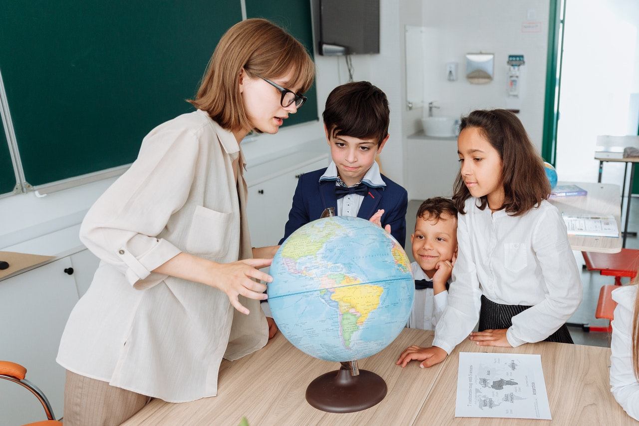 A teacher showing a country on a globe for a small group of students inside a classroom.