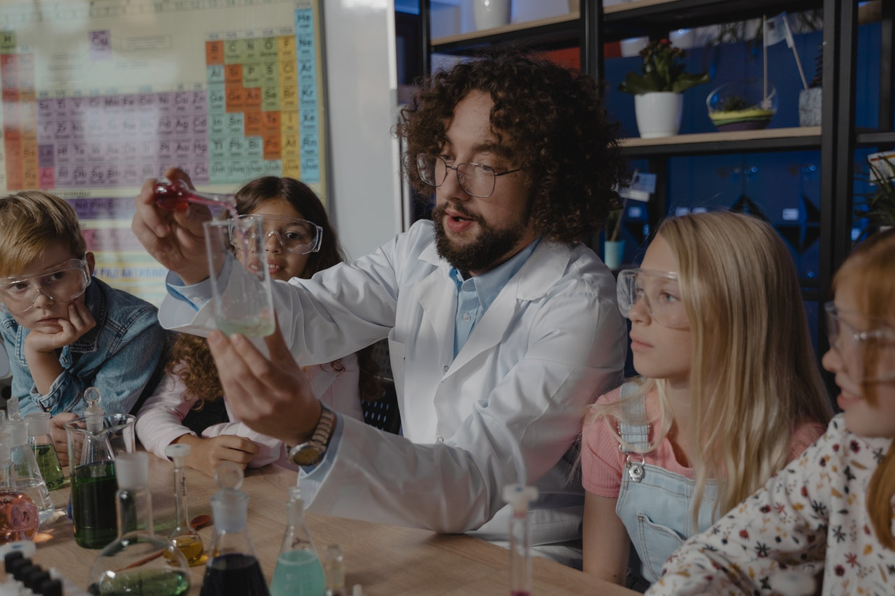 A teacher uses beakers to explain a science project. Students are wearing goggles and a periodic table of elements is visible in the classroom.