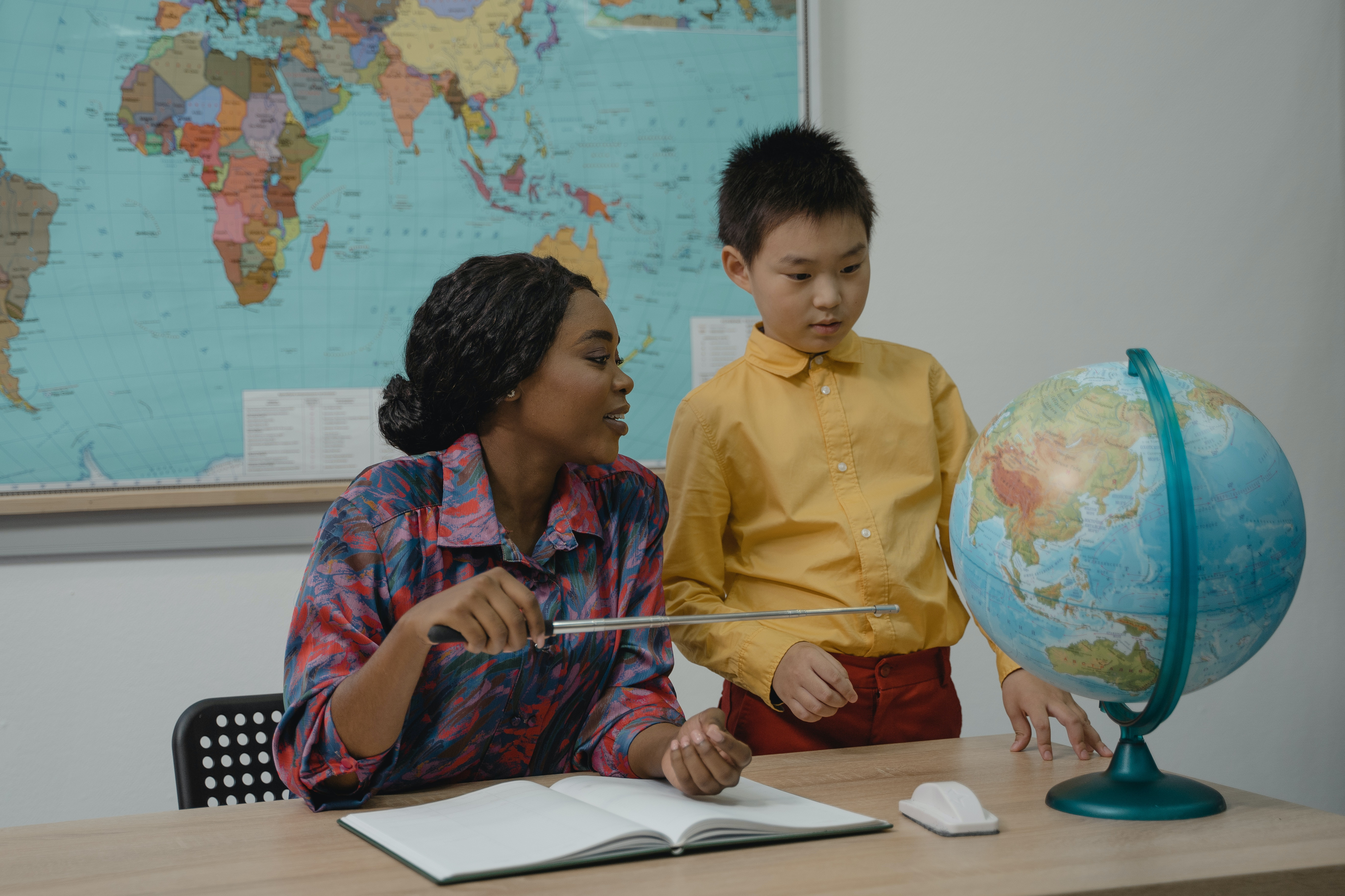 A teacher and a student looking at a globe in a classroom