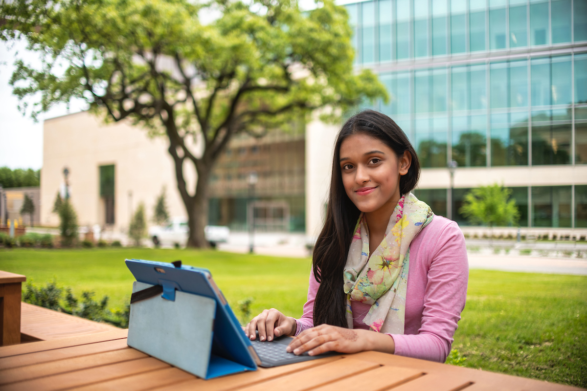 Photo of a student using a tablet to work on the UTA campus