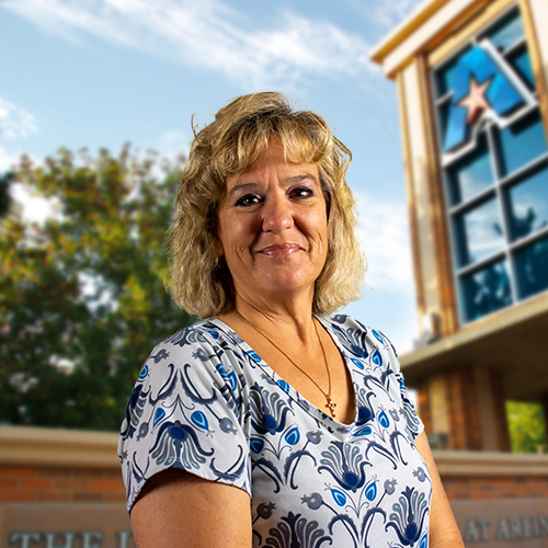 Headshot of University of Texas at Arlington employee Jana Davis. The background shows a UTA campus sign.