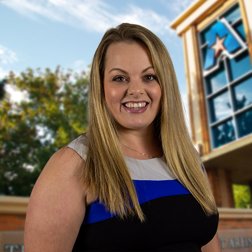 Headshot of University of Texas at Arlington employee Kathleen Ritchie. The background shows a UTA campus sign.