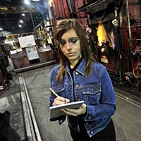 An industrial engineering student takes notes in a factory