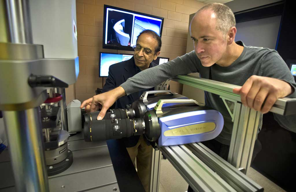 Two professors in mechanical and aerospace engineering demonstrate equipment in a research laboratory.