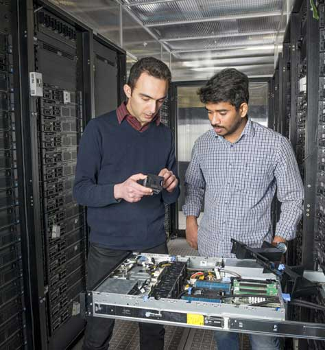 Two researchers examining some electronics in a datacenter.
