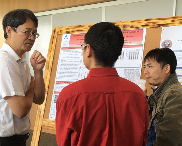 Dr. Liping Tang and Tam Nguyen listen as Duong Le, a Ph.D. candidate in Dr. Nguyen's lab, explains his research.