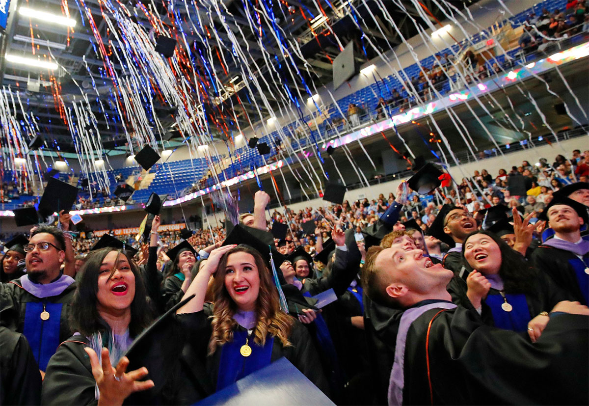 Graduating students tossing their caps at UTA Commencement Ceremony