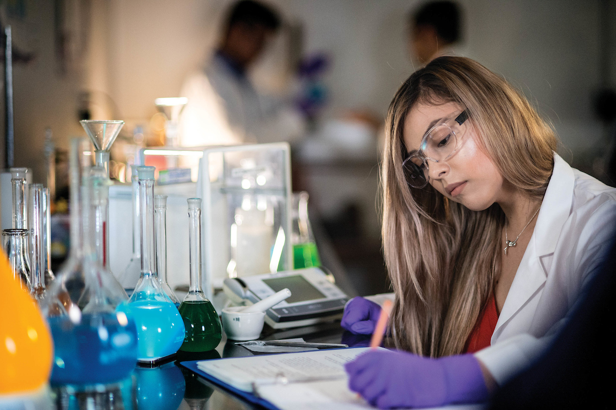 """Student taking notes in research lab"""" _languageinserted=""""true"""