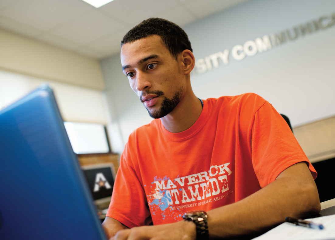 UTA student sitting at a laptop computer