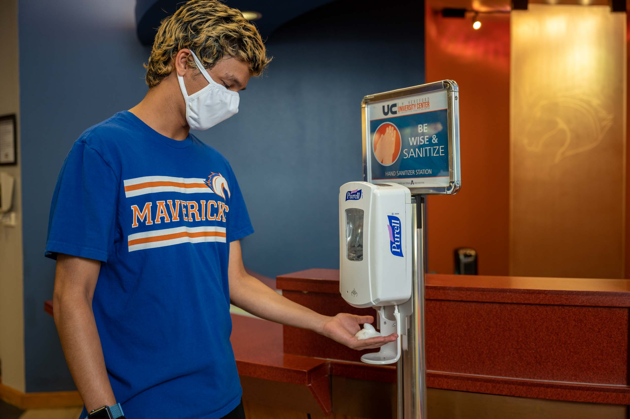 UTA student wearing a mask and using a hand sanitizer dispenser
