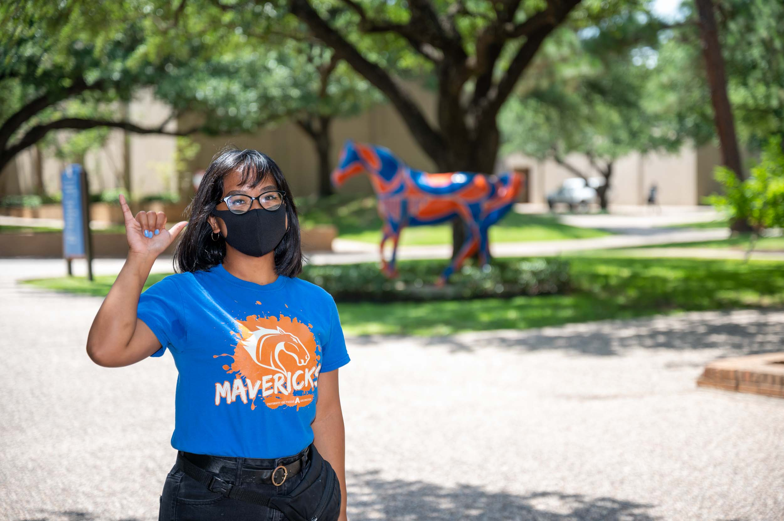 student in mask with spirit horse on campus