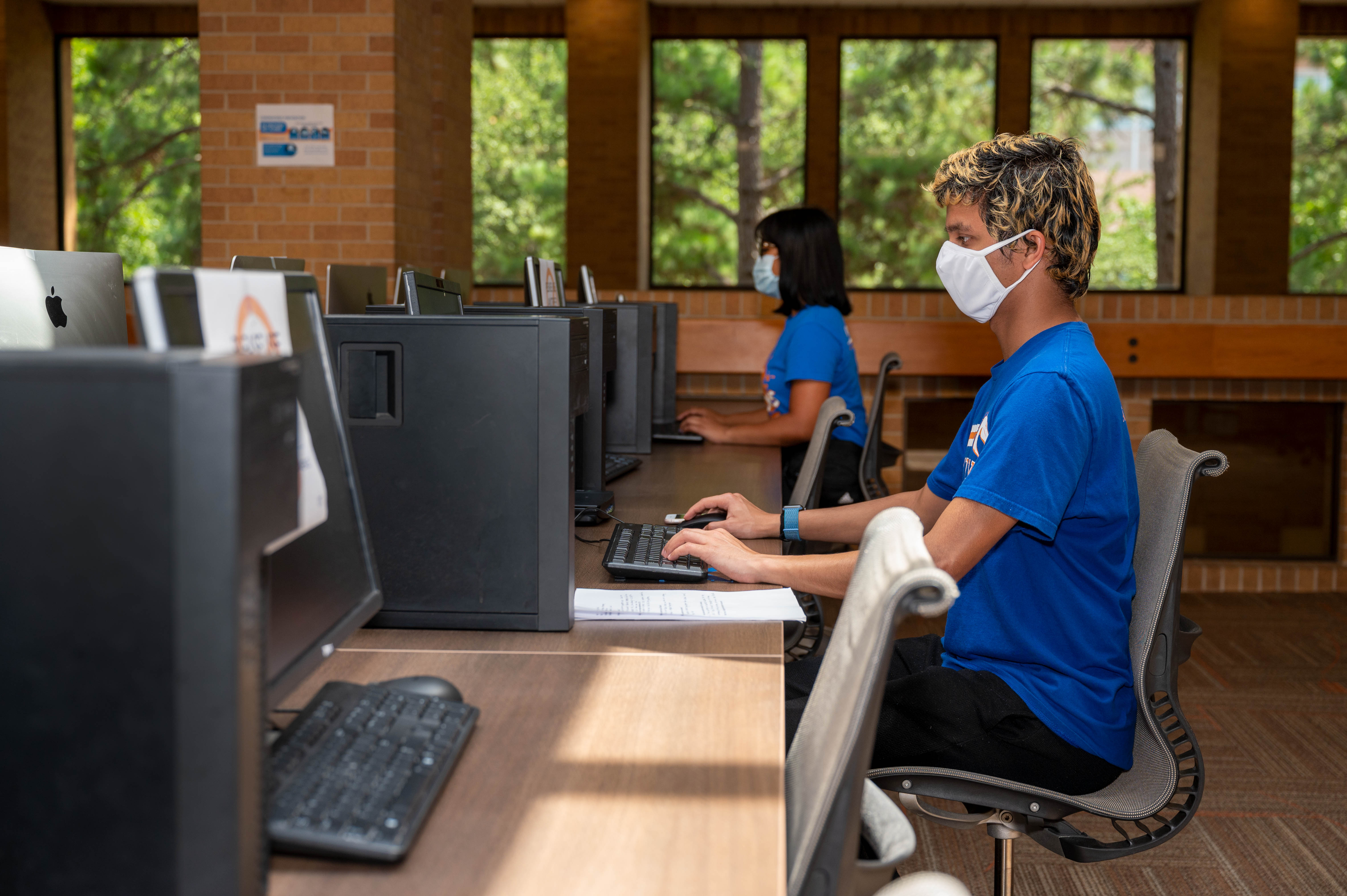 UTA students wearing face coverings in a socially distant computer lab