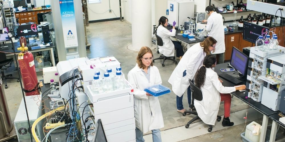 """Researchers in white lab coats conduct experiments in a lab."""" _languageinserted=""""true"""