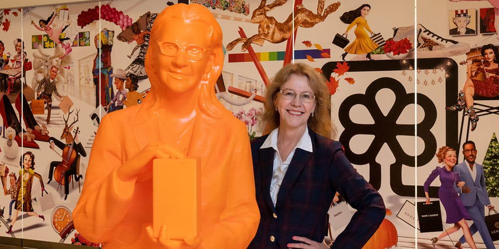 Minerva Cordero, professor of mathematics, stands next to a 3D-printed statue