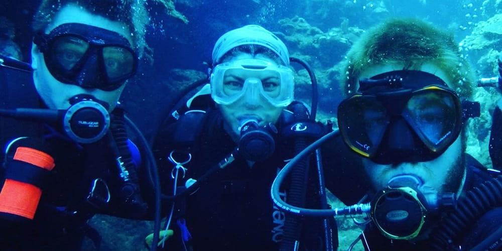 From left, Bradford Dimos, Laura Mydlarz and Nicholas MacKnight diving in Roatan, Honduras.
