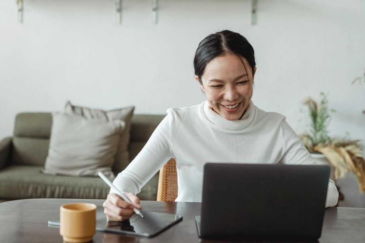 """A woman in an office smiles while working on her laptop."""" _languageinserted=""""true"""
